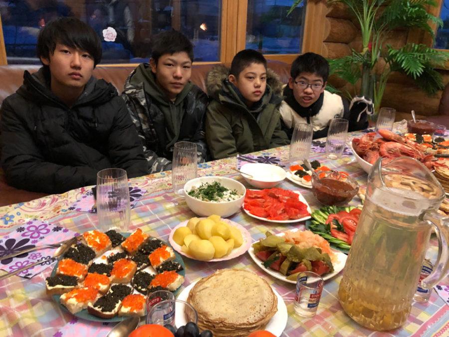 ご馳走の並んだテーブルに座る子供たち